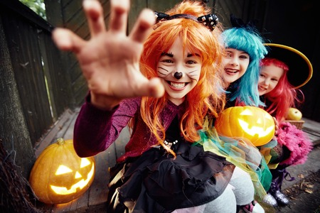of children: Halloween girl looking at camera with her hand in frightening gesture