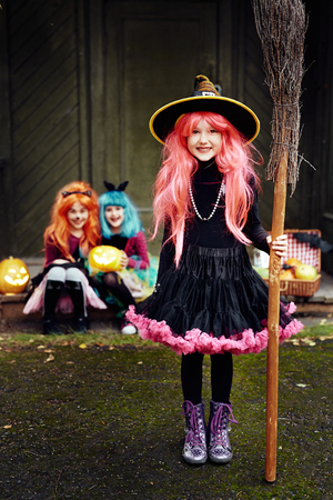 witch on broom: Smiling girl in costume of Halloween witch looking at camera with her friends on background