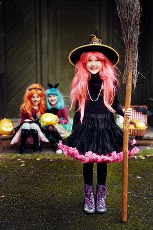czarownica: Uśmiechnięta dziewczyna w stroju Halloween czarownica spojrzenie na aparat fotograficzny z przyjaciółmi w tle