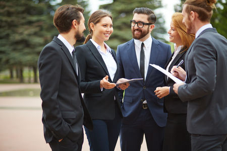 business consulting: Happy young businesswoman talking to colleagues at meeting