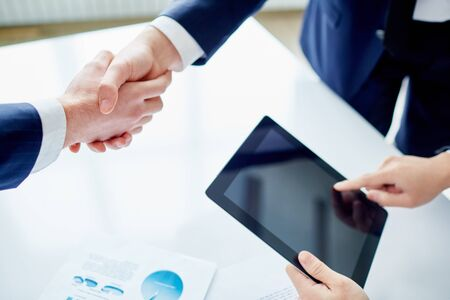 business partnership: Partners shaking hands while businessman with touchpad networking near by