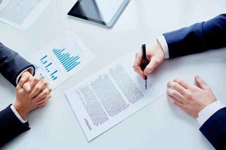 firmando: De negocios que firma un contrato después de hacer un acuerdo