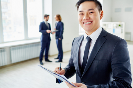 toothy smiles: Elegant young businessman with pen and clipboard making notes