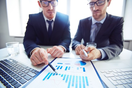 information point: Close-up of two businessmen pointing at chart in document