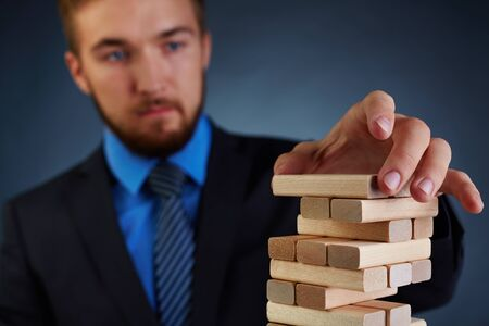 investment ideas: Businessman putting small wooden block on top of tower Stock Photo
