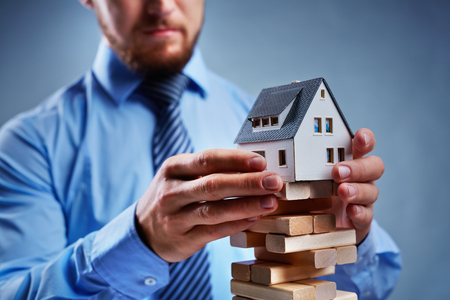 tower house: Businessman putting house model on top of tower from small wooden blocks