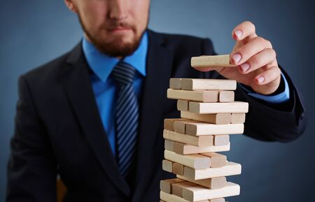 instability: Concept of financial instability: businessman putting small wooden block on top of tower
