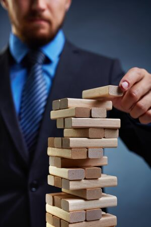instability: Business tower built by small wooden blocks