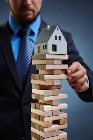tower house: Businessman touching tower from small wooden blocks with house on its top
