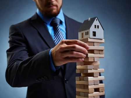 tower house: Businessman touching wooden tower with house on its top Stock Photo