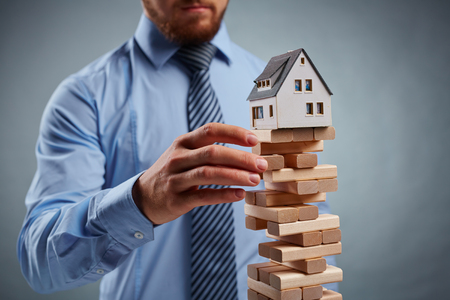 tower house: Businessman taking out wooden block from tower with house model on its top