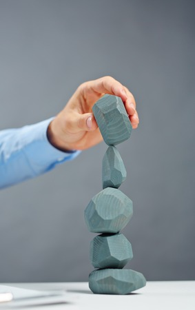 instability: Businessman building tower from grey stones