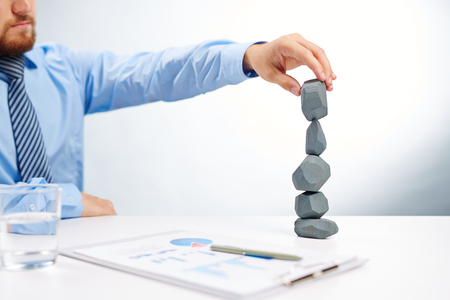 instability: Modern businessman building tower from grey stones on workplace