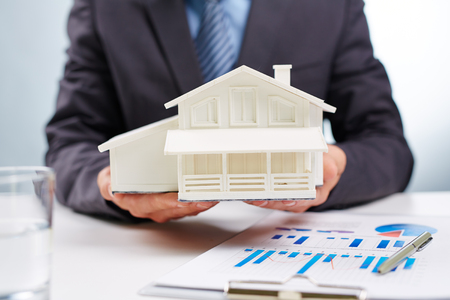 housing loan: Businessman holding toy house Stock Photo