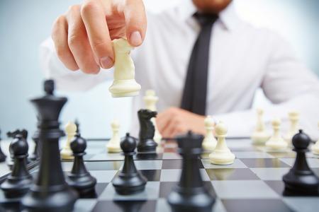 jugando ajedrez: Hombre de negocios con el ajedrez caballero de juego Foto de archivo