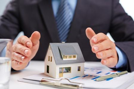 Human open handpalmen op stuk speelgoed huis Stockfoto
