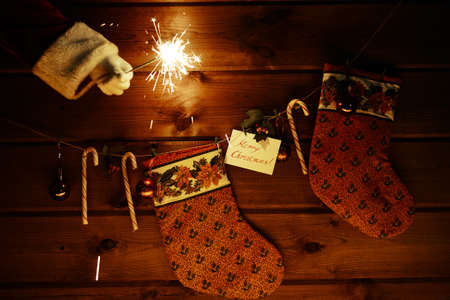 christmastide: Christmas socks, sugar canes, toy bubbles on wooden background and Bengal light in gloved Santa hand