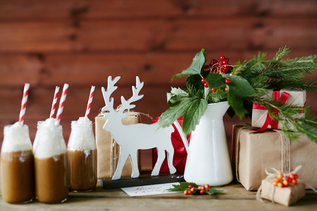 guelder: Toy deer, porcelain vase with guelder leaves and berries, bottles with hot chocolate topped with whipped cream and giftboxes on table in cafe Stock Photo