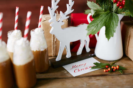 guelder: Wooden deer, porcelain vase with guelder leaves and berries, bottles with hot chocolate with whipped cream and gifts on table Stock Photo
