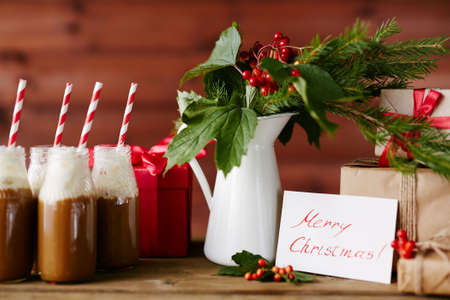 guelder: Vase with guelder leaves and berries, bottles with hot chocolate topped with whipped cream and several giftboxes Stock Photo
