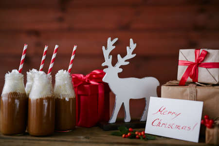 christmastide: Toy deer, bottles with hot chocolate topped with whipped cream and giftboxes Stock Photo