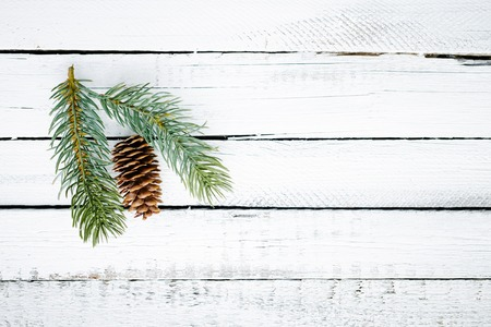 christmastide: Firtree cone and conifer over wooden background Stock Photo
