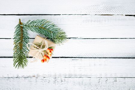 conifer: Gift in package and evergreen conifer branches over wooden background Stock Photo