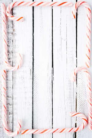 christmastide: Several candy canes making frame over wooden background