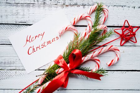 regards: Christmas bouquet and greeting card on wooden background