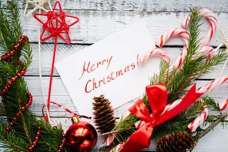 christmastide: Christmas composition made up of conifer branches, cones, decorative bubble, stars, beads, candy canes and greeting card on wooden background