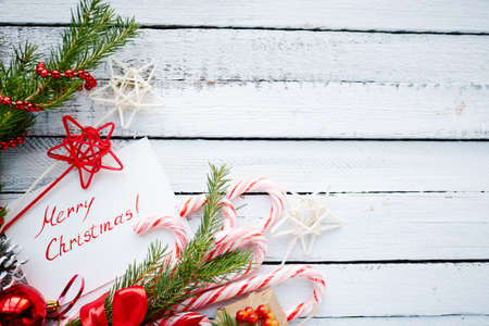 christmastide: Christmas decorations and greeting card on wooden background