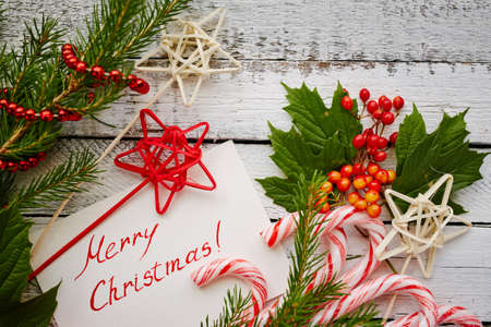 christmastide: Christmas canes, decorations and greeting card on painted wooden background