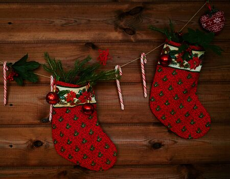 merry  christmas: Christmas socks, sugar canes, toy bubbles and other decorations on wooden background Stock Photo