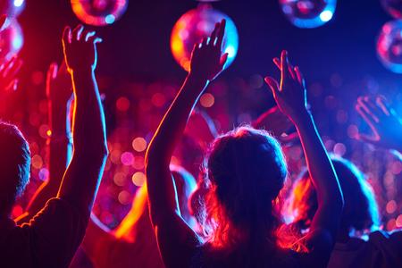 Groep jonge mensen met opgeheven armen dansen in nachtclub