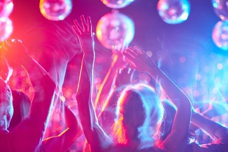 gente bailando: Multitud de personas con los brazos levantados bailando en club nocturno