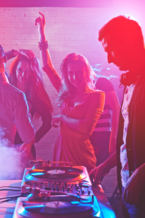turntables: Dancing girls enjoying party by turntables of deejay adjusting sound Stock Photo