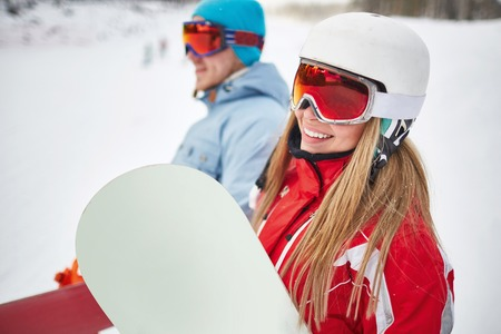 activewear: Happy young snowboarder in activewear looking at camera on background of her boyfriend on winter resort