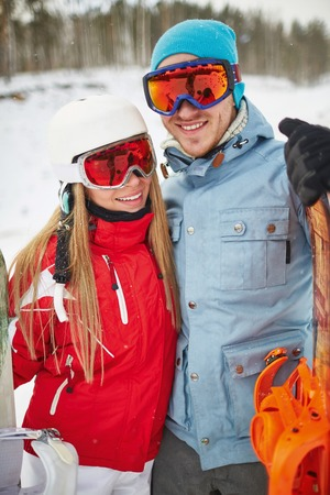 activewear: Couple of happy snowboarders in winter activewear looking at camera on resort