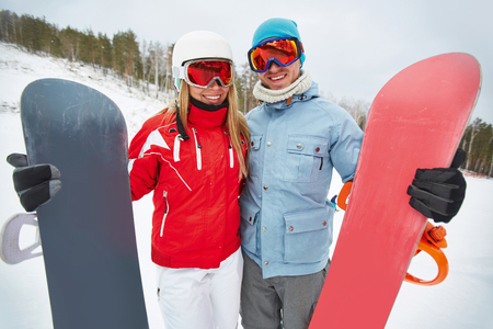activewear: Contemporary snowboarders in winter activewear and goggles looking at camera on resort