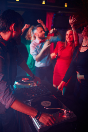 turntables: Modern deejay adjusting sound on turntables with group of dancing girls near by
