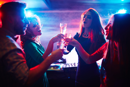 cheers: Cheerful friends toasting at party in night club Stock Photo