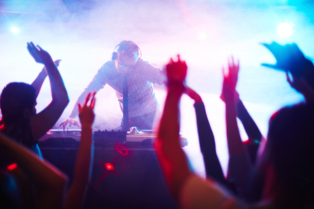 energetic: Energetic deejay standing by turntables in front of dancing crowd Stock Photo
