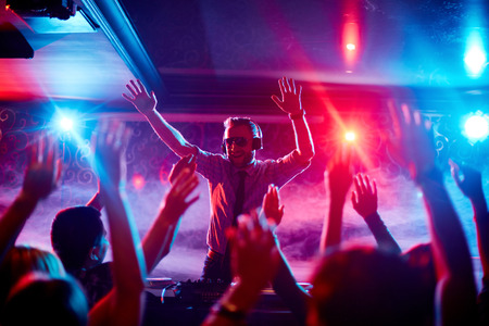 clubber: Energetic deejay with headphones having fun by turntables in front of dancing crowd