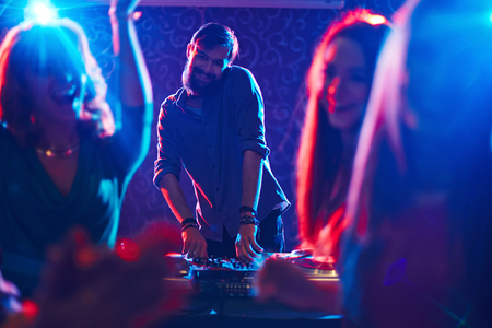 turntables: Happy bearded deejay standing by turntables in front of dancing crowd and looking at camera Stock Photo