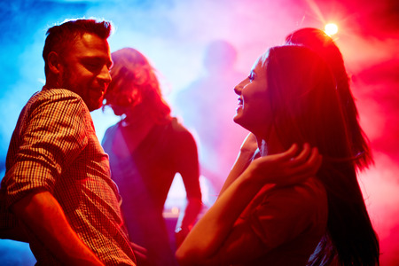 disco: Happy young couple dancing at party in disco club Stock Photo