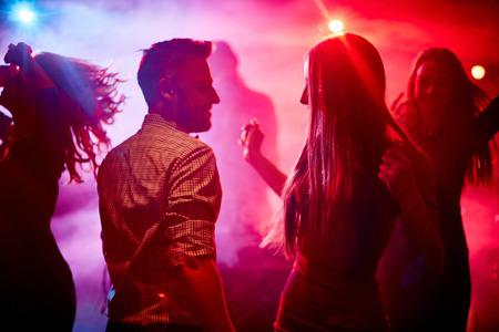 행복한 커플과 디스코 클럽에서 춤을 자신의 친구