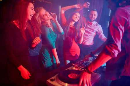turntables: Cute girls dancing by turntables and dj adjusting sound Stock Photo
