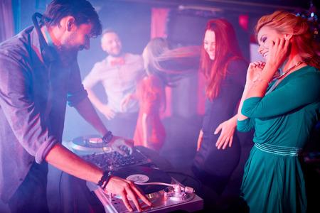 party dj: Muchachas atractivas que bailan por dj sonido ajustando en placas giratorias en club nocturno