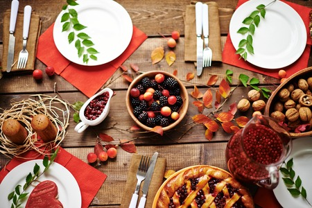 Fresh rennets, walnuts, pastry, jam, fruit drink, berries and tableware on served table Stock Photo