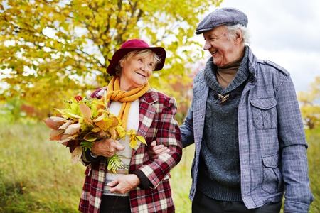 Romantic seniors taking walk in park in autumn Stock Photo